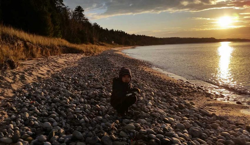 A young rock hound explores the beach near Cross Village (Photo: Jeremy Hammond)